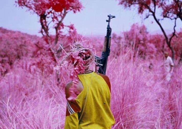 Richard Mosse. Drag, 2012. Soldat fra Mai Mai Yakutumba-militsen slæber en anden soldat gennem græsset i en kampsimuleringsøvelse, i nærheden af South Kivu, Demokratisk Republik Congo. © Richard Mosse. Courtesy kunstneren, Jack Shainman Gallery & carlier | gebauer